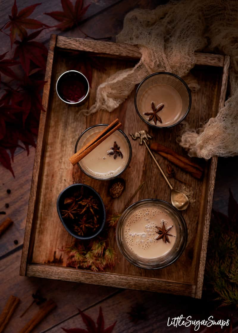 glasses of spiced tea on a tray with a shot of rum. Cinnamon and star anise served alongside.