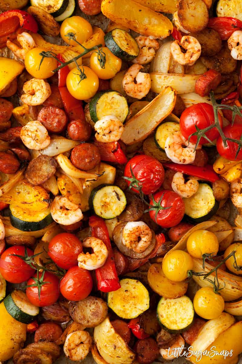 sheet pan chorizo and prawn dinner with onion, baby tomatoes, red and yellow peppers and courgette