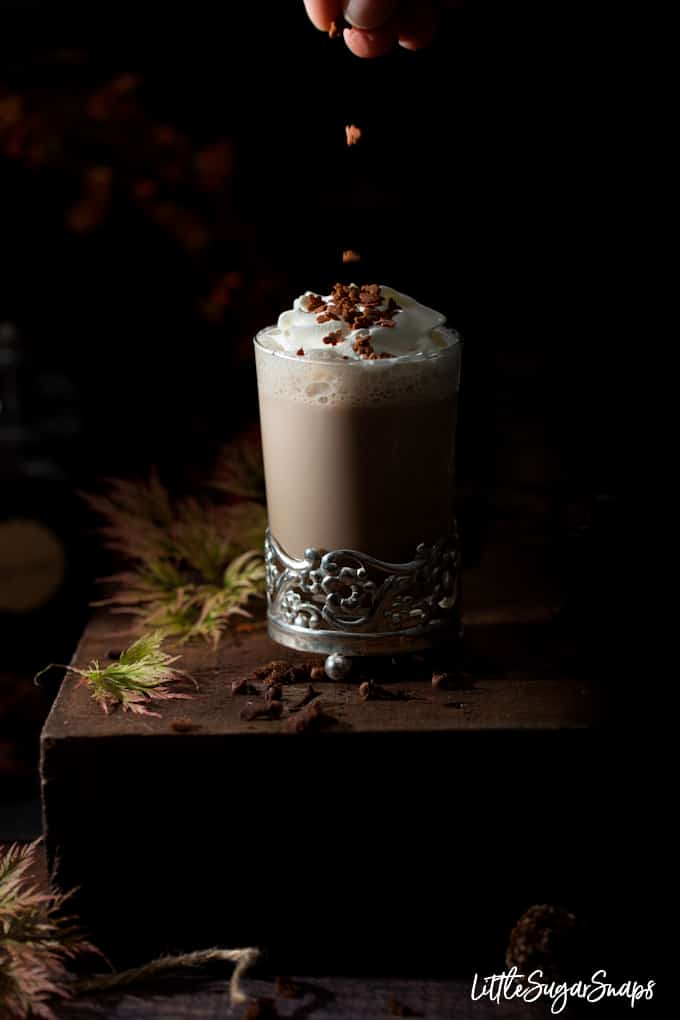 milky gingerbread latte drink topped with cream and gngerbread shaped spinkles being added. Dark and moody setting with autumn leaves around.