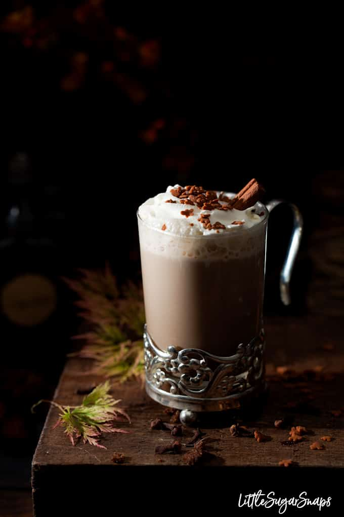 A glass of gingerbread latte decorated with whipped cream and gingerbread shaped sprinkles
