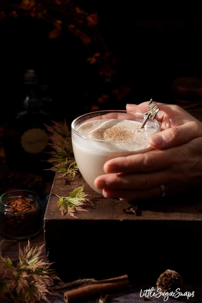 spiced mil steamer topped with nutmeg in a glass mug being picked up. Cosy autumn scene - moody lighting and autumn foliage around