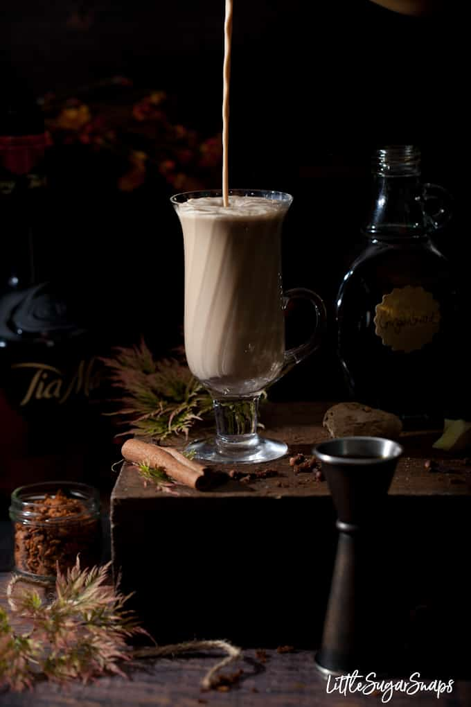 milking coffee being poured into a vintage coffee glass with cinnamon and autumn foliage around