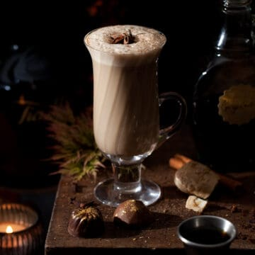 A glass of milky gingerbread latte in a vintage glass topped with ground spice and a piece of star anise. Several chocolates are in front of the glass