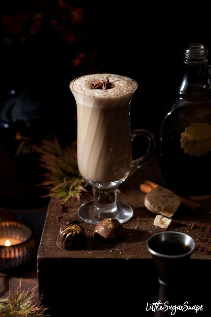 boozy gingerbread latte spiked with coffee liqueur in a vintage glass with frothy milk and grated nutmeg & star anise garnish