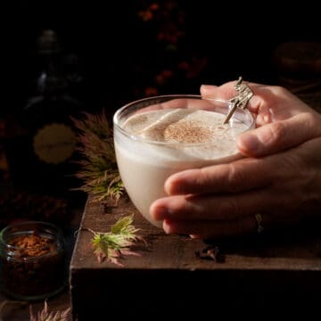 Person holding a glass mug of milky drink. Mug is on a wooden table and there is autumn foliage around it and the drink has a sprinkle of spice on the top