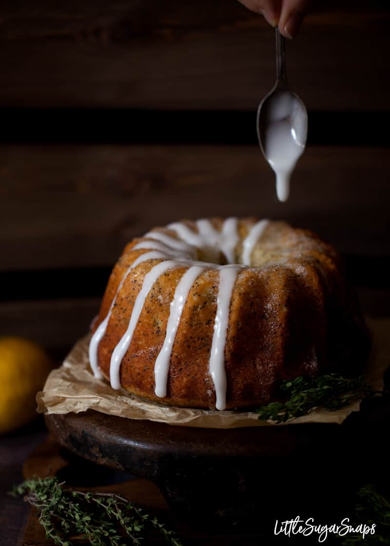 lemon icing being spooned over a circular cake sitting on a wooden stand and parchment