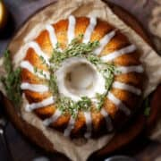 Fully decorated lemon bundt cake topped with water icing and fresh thyme. Top down view of the uncut cake