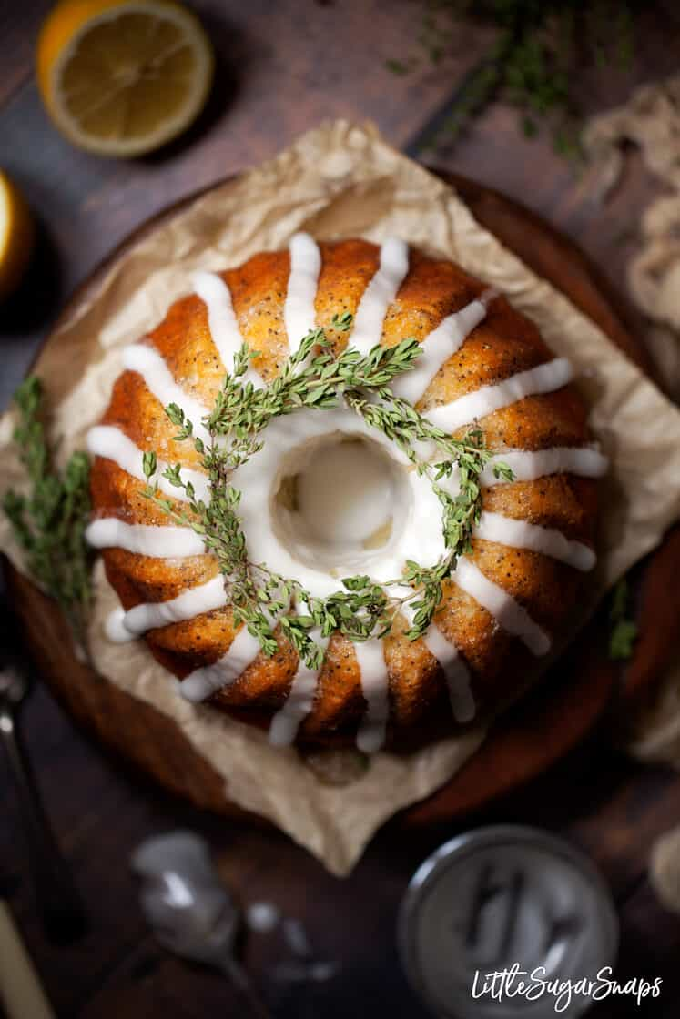 Overhead view of a bundt cake with water icing and thyme garnish.