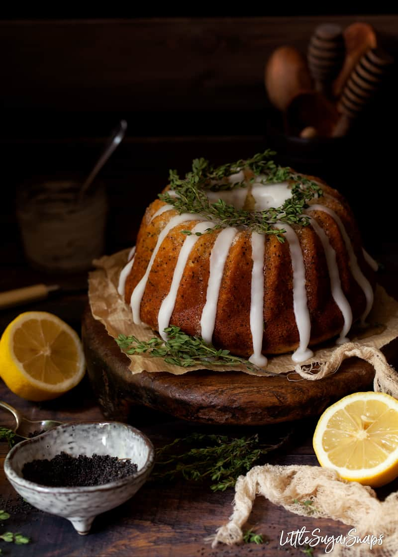 lemon and poppy seed bundt cake decorated with lemon glace icing and thyme leaves in a rustic setting with a bowl of poppy seeds and lemon nearby