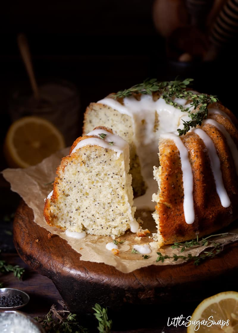 a slice of lemon and thyme cake speckled with poppy seeds with lemons and thyme in the picture