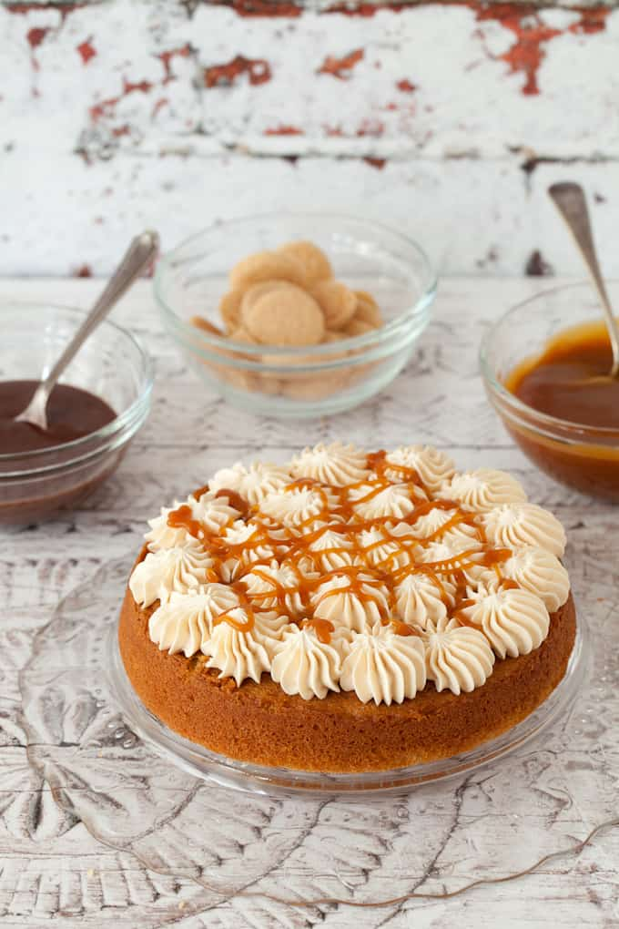 decorating a millionaire's cake. bottom layer of sponge cake has rosettes of buttercream on top and caramel sauce drizzled over it. Pots of caralem & chocolate sauce behind along with shortbread cookies