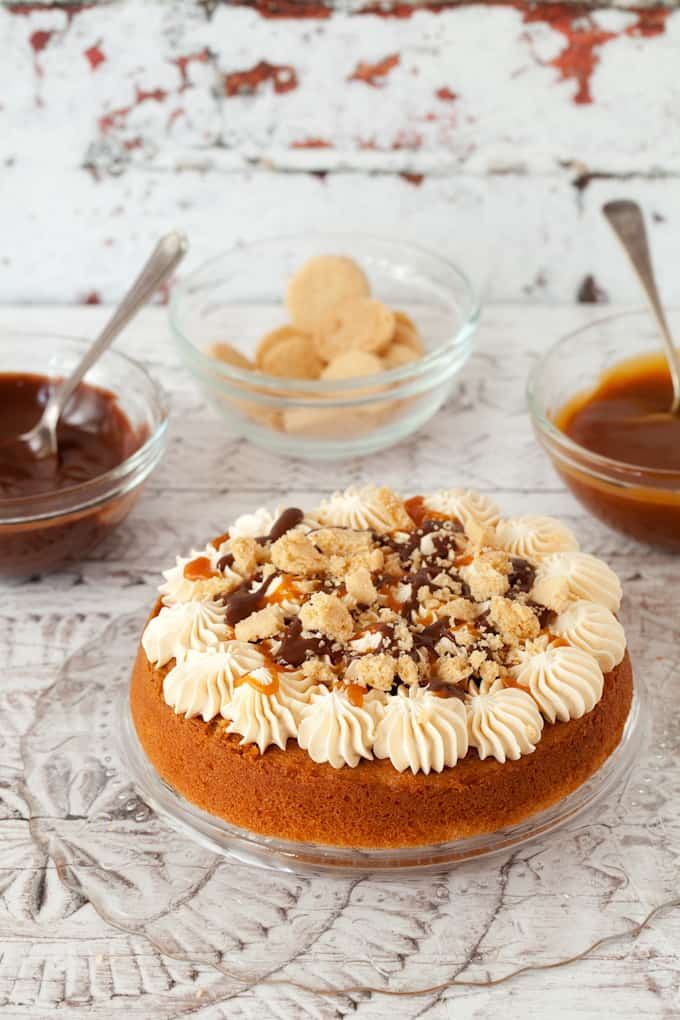 decorating a millionaire's cake. bottom layer of sponge cake has rosettes of buttercream on top, chocolate & caramel sauce and chunks of shortbread cookies on top. Pots of caramel & chocolate sauce behind along with shortbread cookies