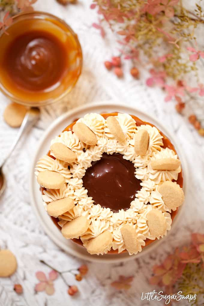 millionaire's shortbread cake decorated with Italian buttercream, chocolate ganache, mini cookies and caramel sauce. With a bowl of caramel sauce and pink flowers in shot.