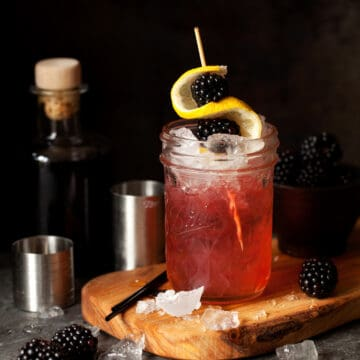 A bramble cocktail with blackberries and lemon garnish