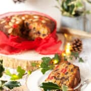 A slice of Christmas Cake on a plate in front of the entre cake. It's a cake that can be made at the last minute and so is simply decorated with with almonds and glace cherries and tied with a red ribbon. Holly, ivy and fairy lights are in shot to give a festive feel