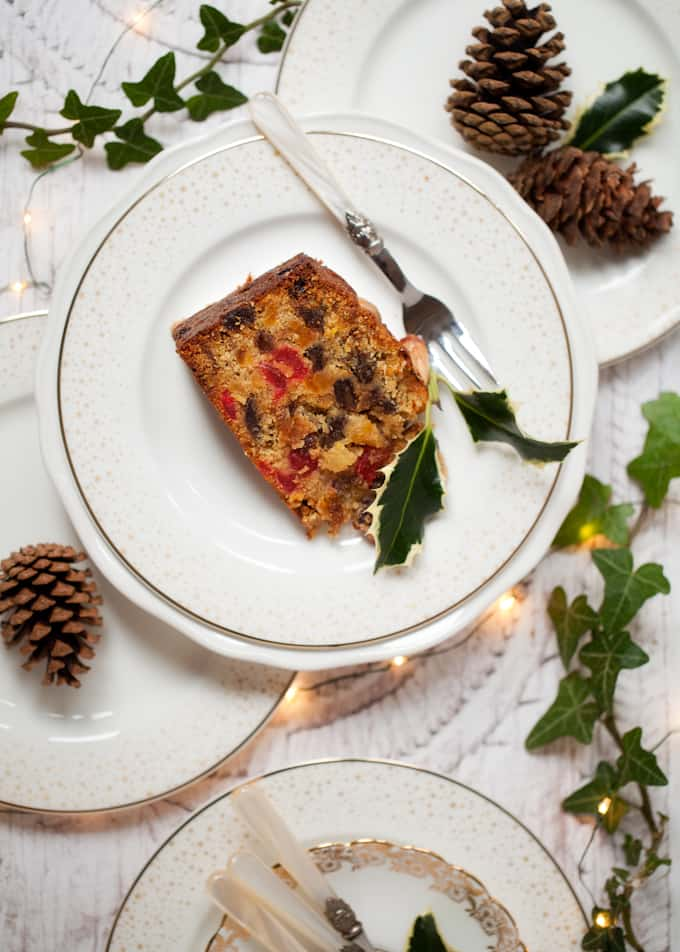 A slice of fruit cake with holly and ivy leaves and fairy lights on white crockery