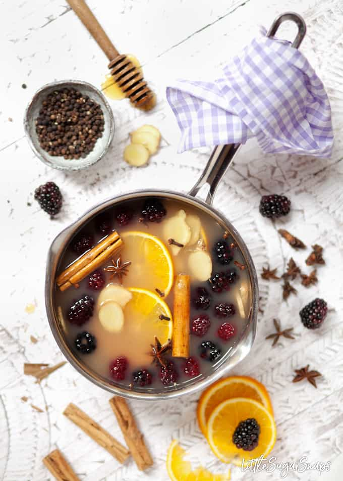 A pan filled with apple juice and mulling ingredients like cinnamon and star anise, orange slices and blackberires still in the pan and ingredients scattered around