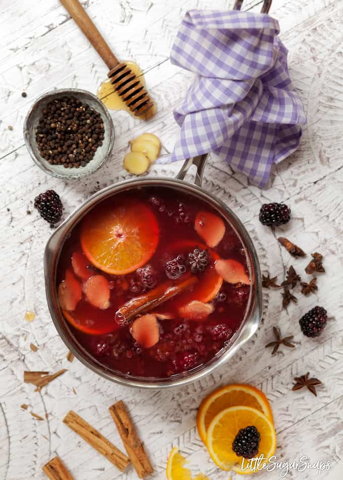 A pan full of mulled apple and blackcurrant juice. It has mulling ingredients like cinnamon and star anise, orange slices and blackberires still in the pan and ingredients scattered around