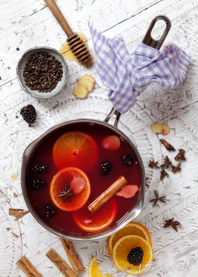 mulled apple juice with blackberries - juice and ingredients in a pan with orange slices, cinnamon, fresh ginger and blackberries