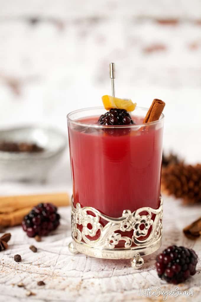 Hot mulled fruit juice in vintage glassware with cinnamon, star anise and blackberry garnish