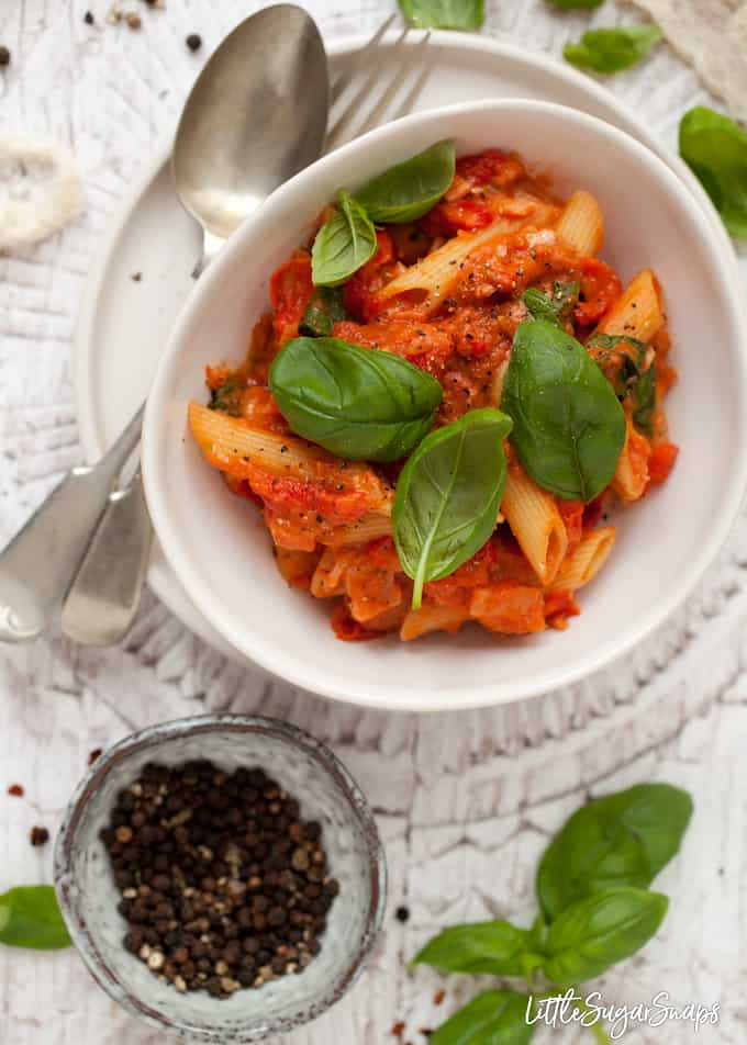 Pasta in a creamy tomato sauce with basil leaves in a white bowl