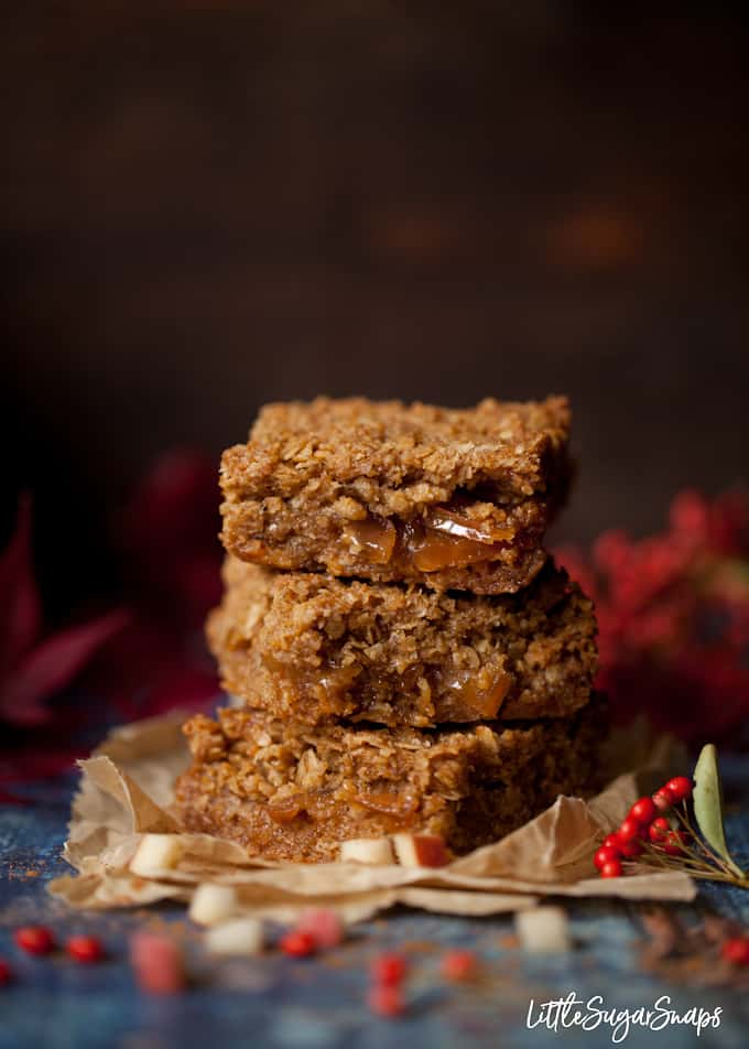 a stack of 3 toffee apple flapjack bars on parchment paper with red foliage in shot