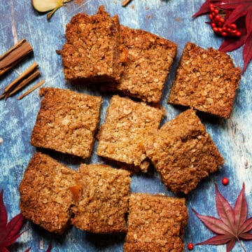 Nine pieces of flapjack on a blue background with slices of apple, cinnamon and autumn leaves and berries surrounding it