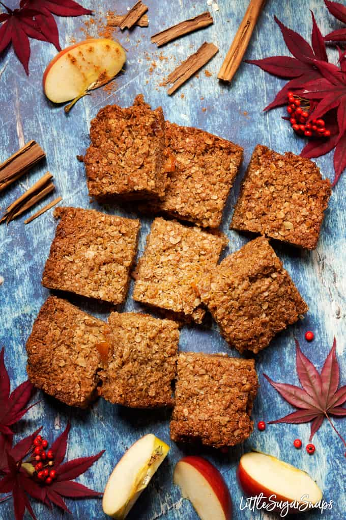 Oat bars filled with toffee apple sauce on a blue background, cut into squares with fresh apple and cinnamon in shot