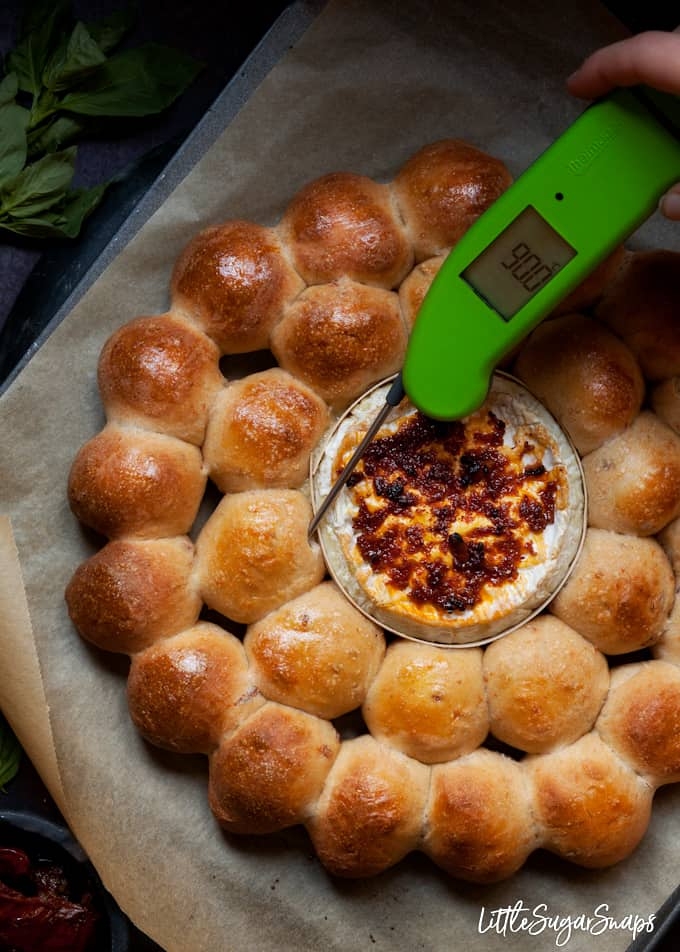 Green food thermometer being used to test that dough balls on a baked camembert cheese platter are cooked through
