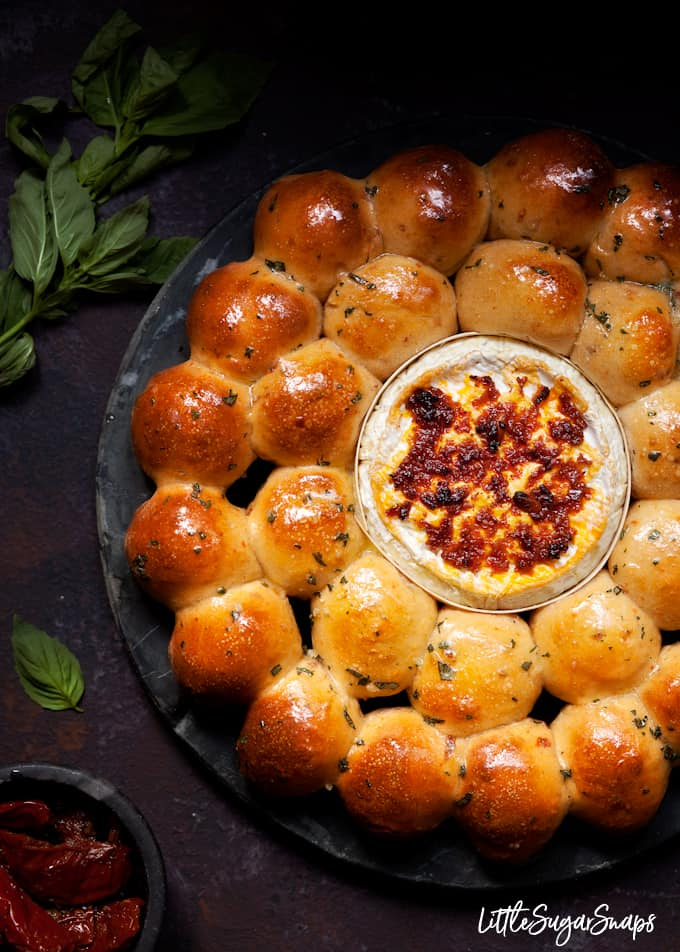 Freshly baked garlic butter dough balls with baked camembert and red pesto