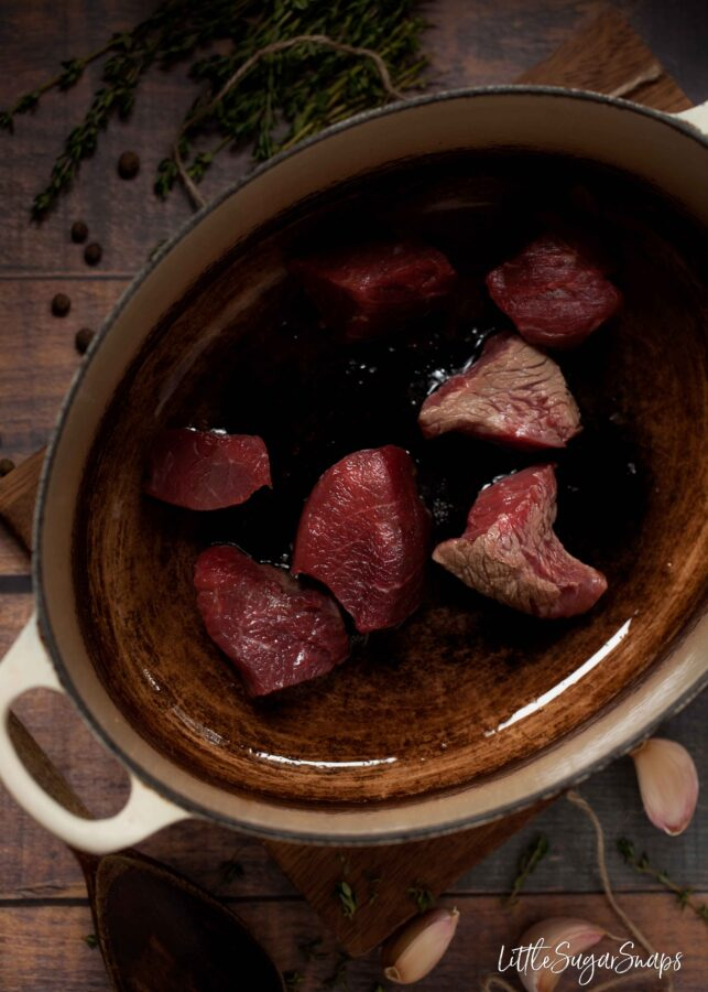 beef chunks being browned in a cast iron pan