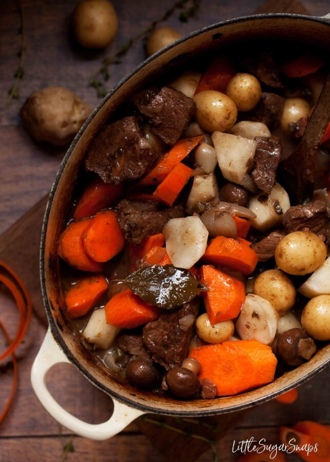 Root vegetables being added to a casserole pan