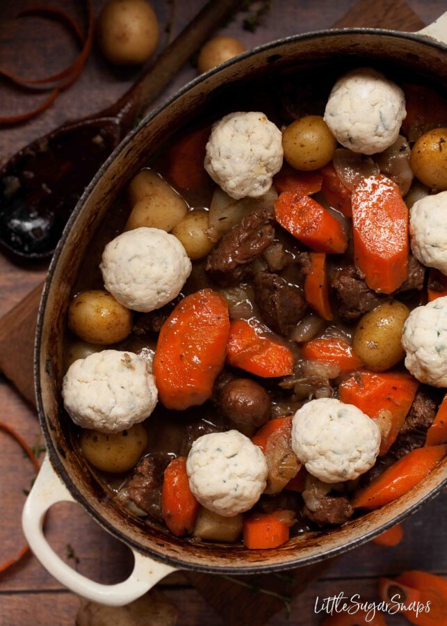 Uncooked blue cheeese dumplings topping a hearty stew in a cast iron pan