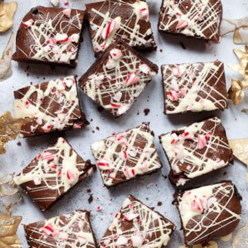 Squares of Candy Cane Brownies topped with white chocolate and chunks of candy cane on a grey worktop