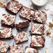 12 squares of peppermint browneis topped with white chocolate and crushed candy cane. One piece is on its side to reveal mint fondant in the middle