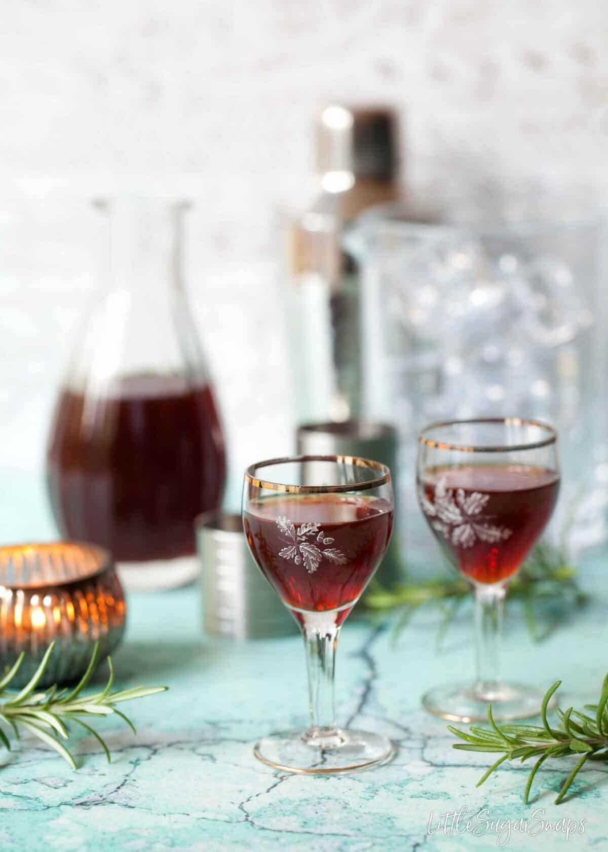 Vintage glasses of sloe gin with a small decanter of sloe gin in the background