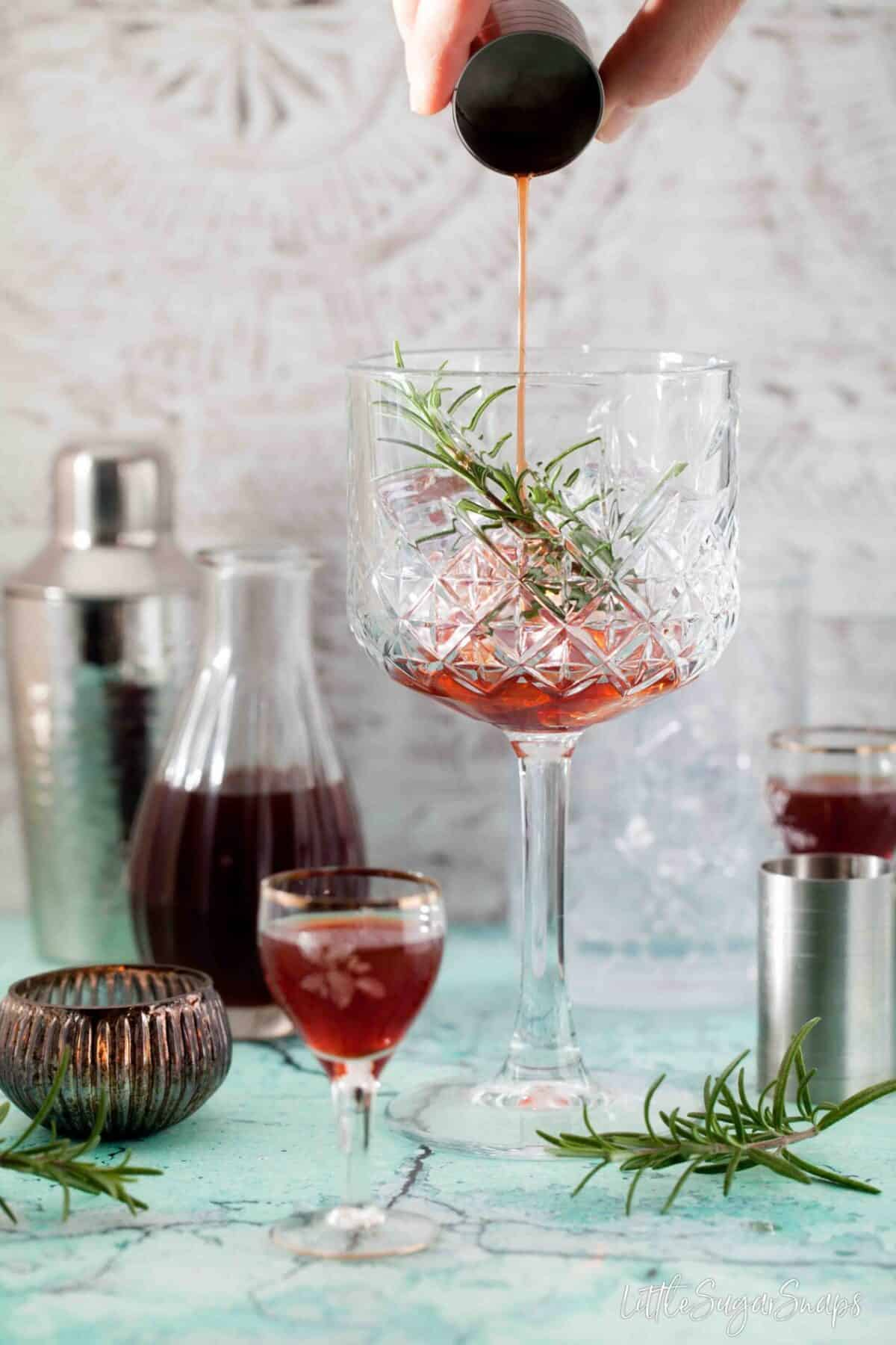 pouring sloe gin into a copa glass