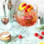 A winter version of aperol spritz with sloe gin and rosemary. Garnished with orange and raspberries