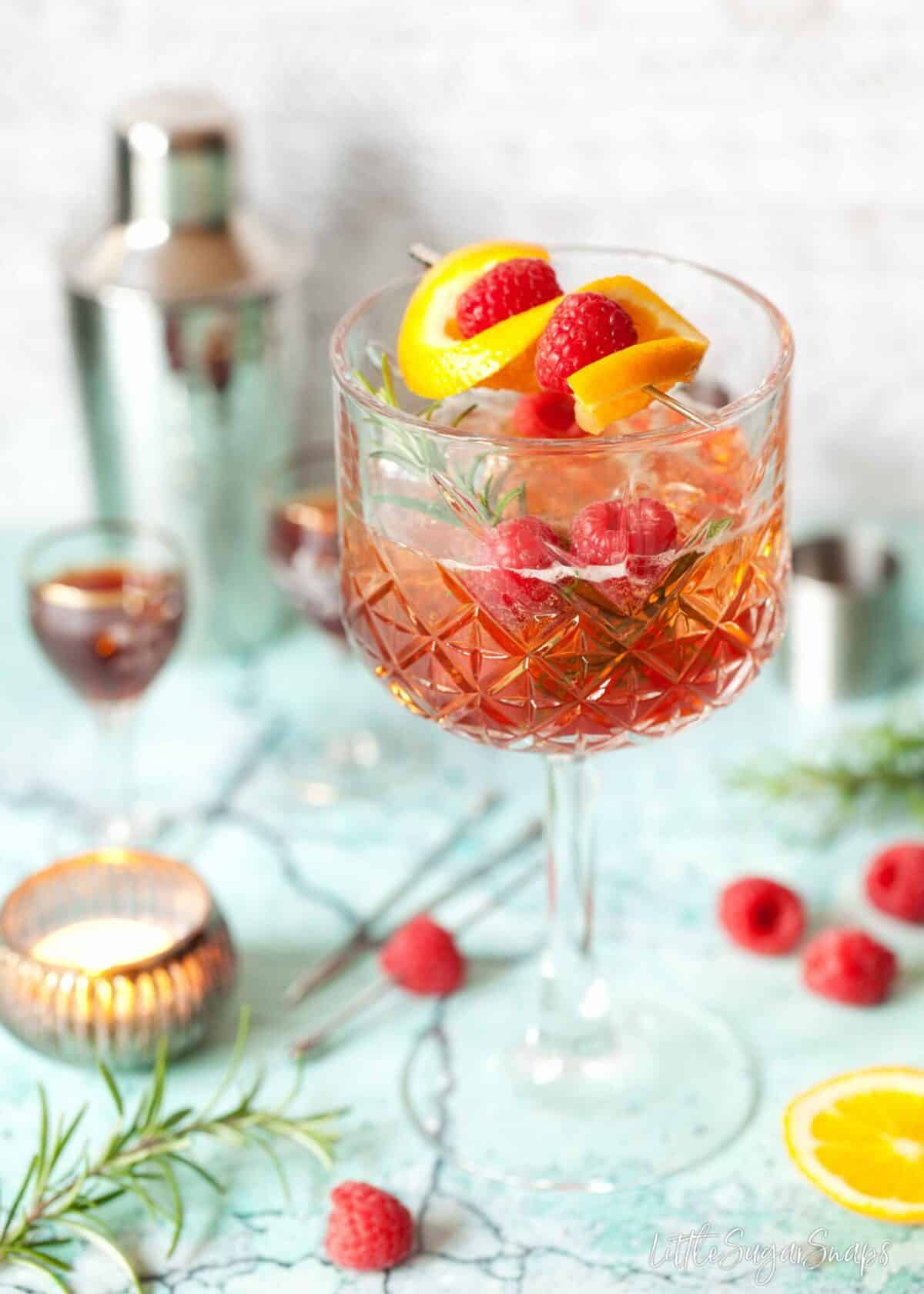 a winter aperol spritz with sloe gin, garnished with orange, raspberry and rosemary