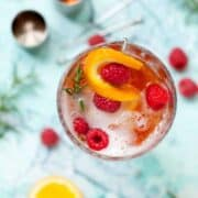 overhead view of a winter aperol spritz with sloe gin and rosemary