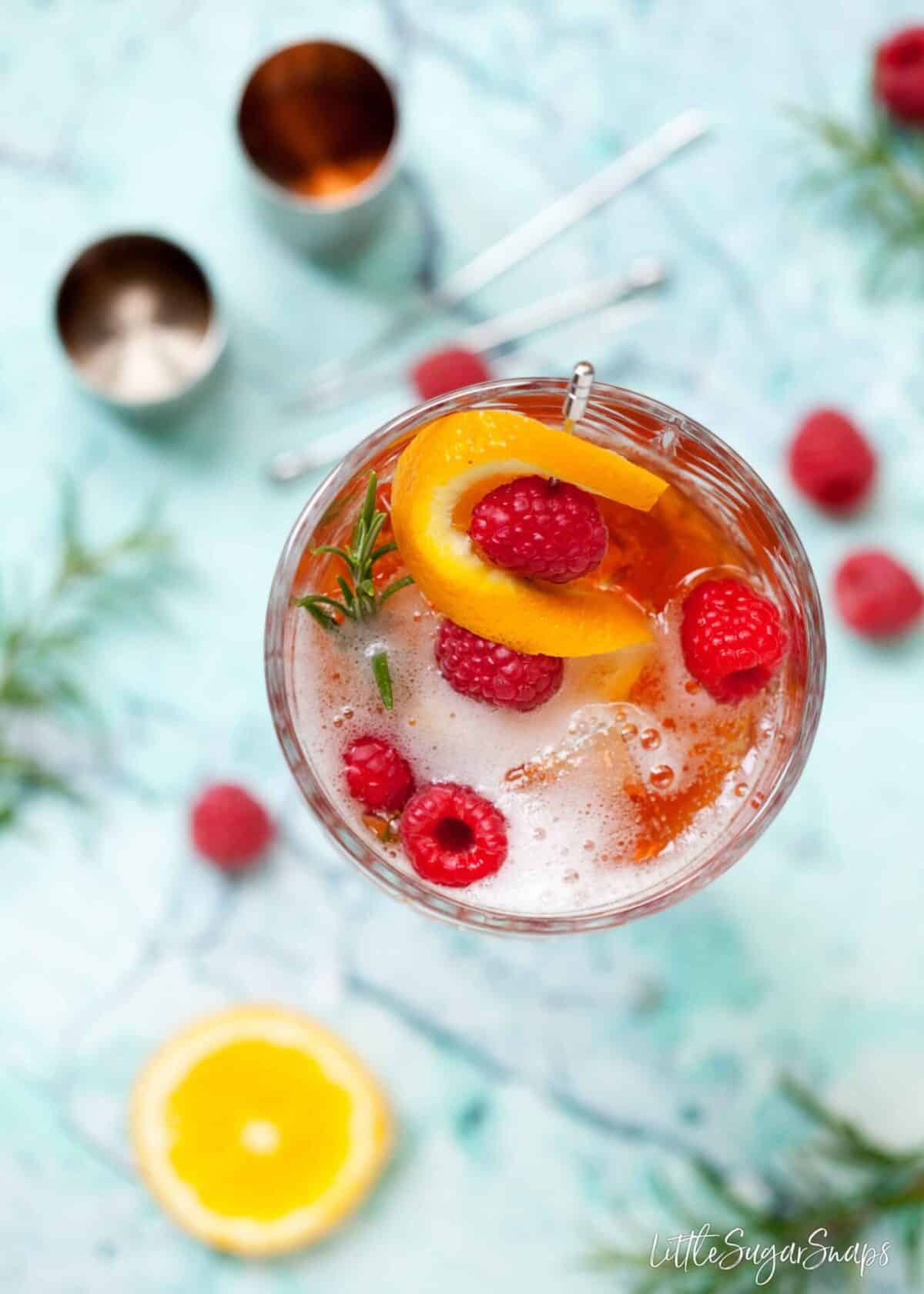 overhead view of aperol spritz recipe made with sloe gin. garnished with orange, raspberry and rosemary