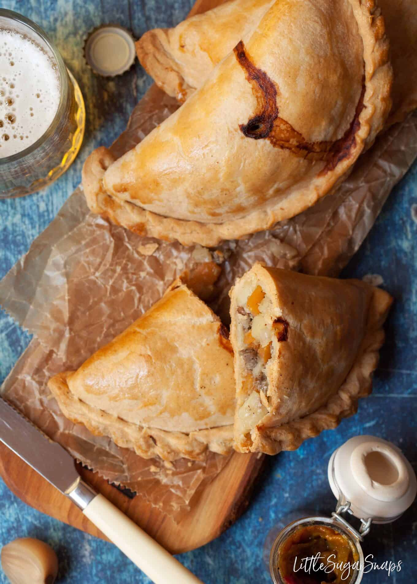 meat and vegetable pasties - one cut open to reveal the filling on a wooden serving platter with beer and relish