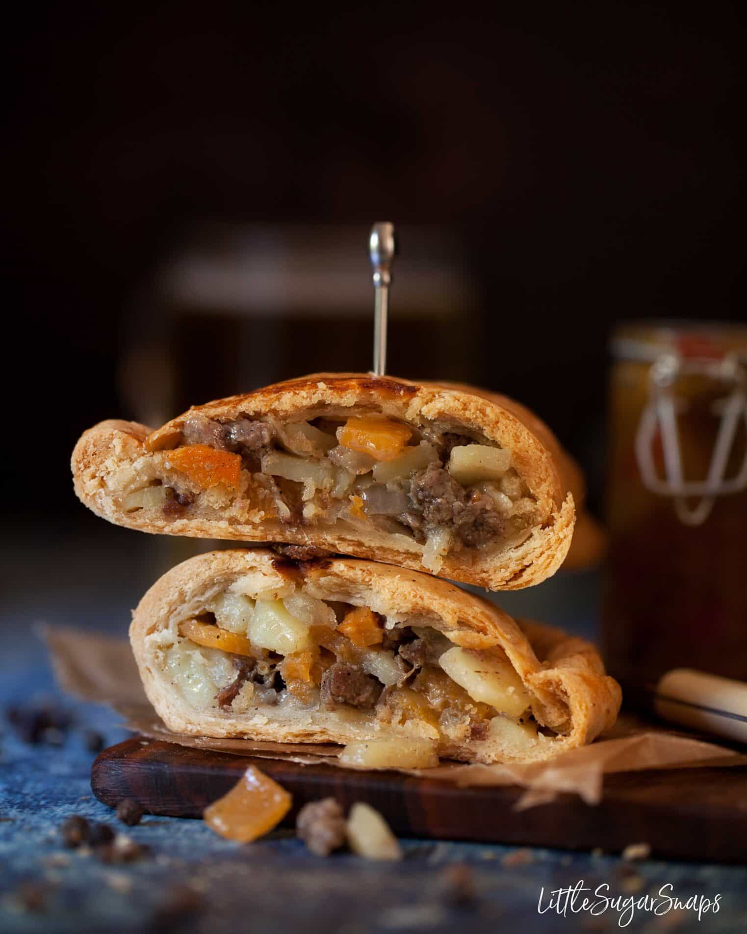 Traditional Cornish pasty cut in half and stacked on top of each other.