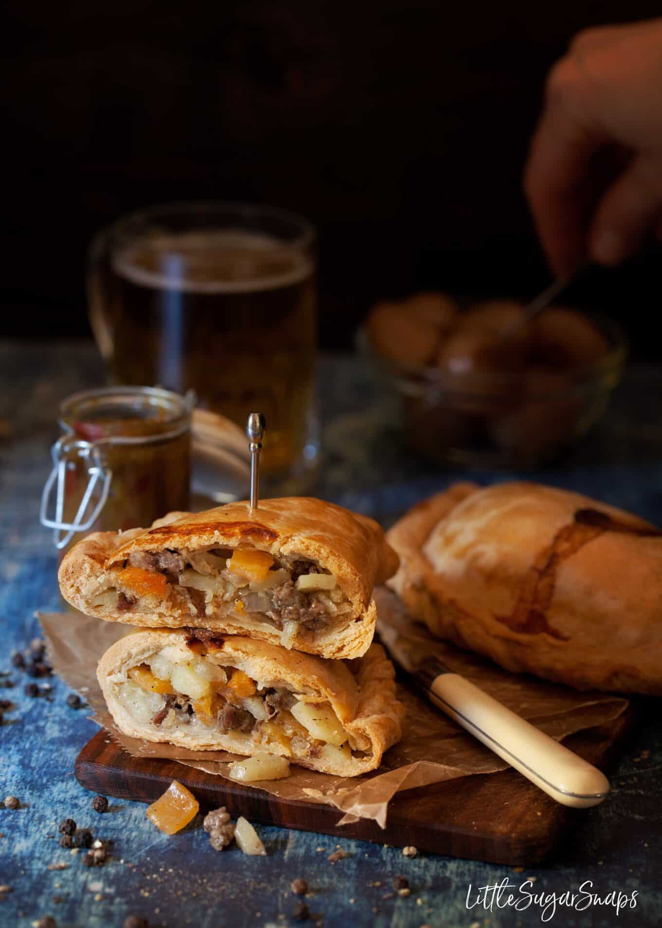 beef and horseradish pasties cut in half and stacked on top of each other to reveal meat, onion, potato and swede (rutabaga) inside with relish and beer in the background