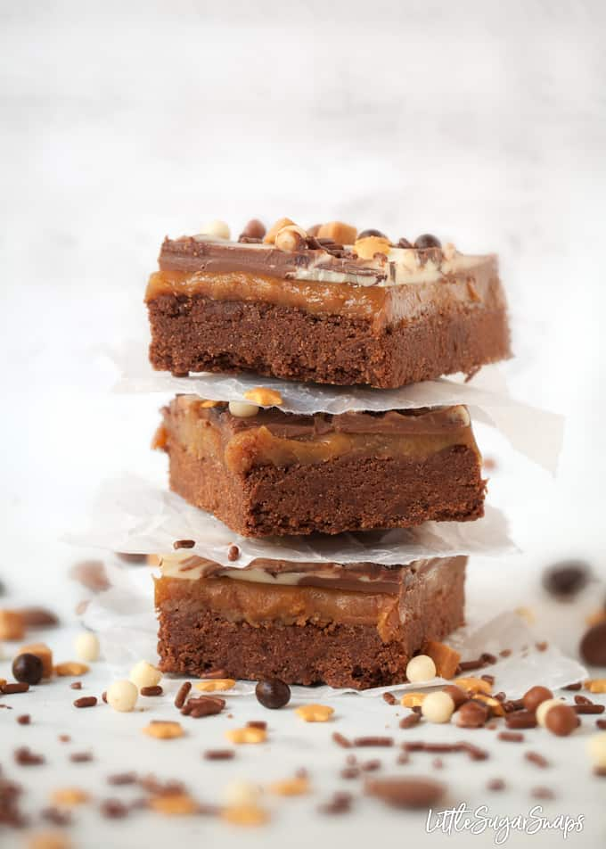 A stack of 3 Chocolate Caramel Shortbread Bars with chocolate and caramel sprinkles on the worktop.