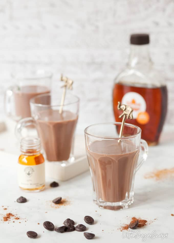 Bourbon Hot Chocolate in glasses with bottles of bourbon and maple syrup alongside.