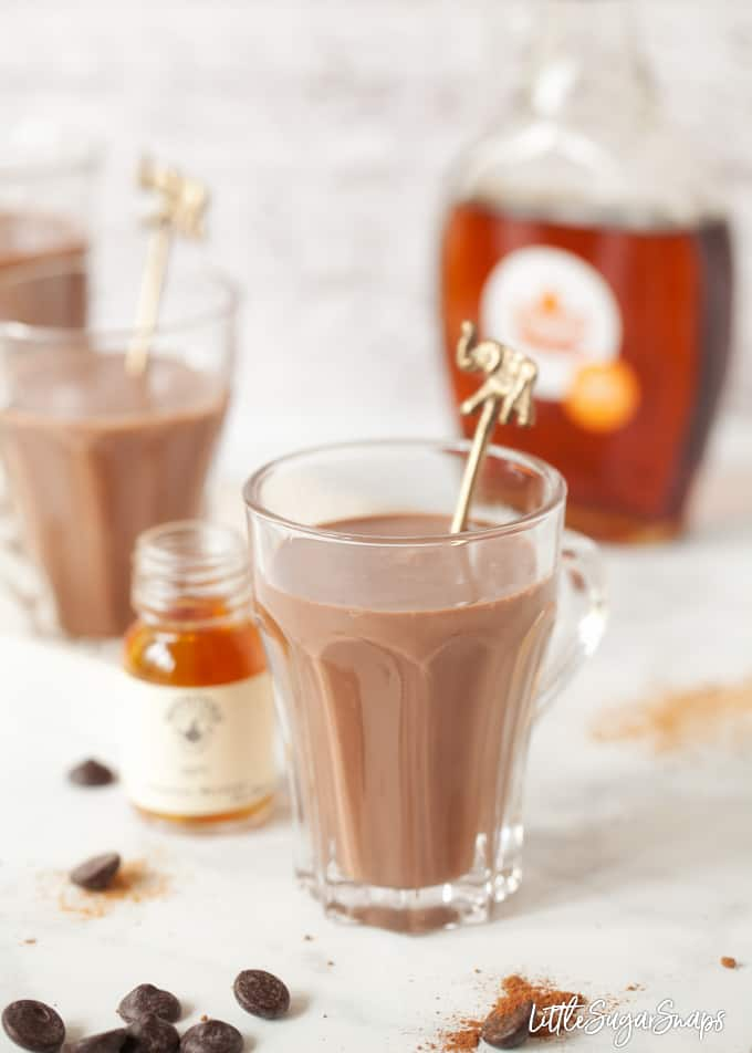 A glass of hot chocolate with bottles of maple syrup and bourbon alongside