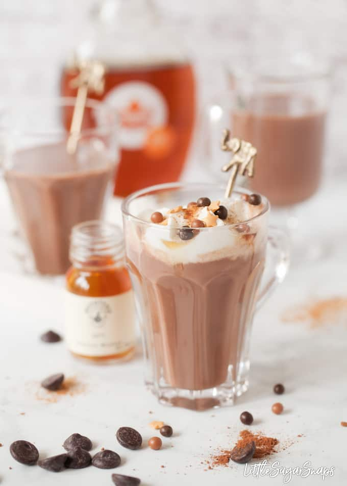 Hot chocolate topped with cream and sprinkles with bottles of bourbon in shot