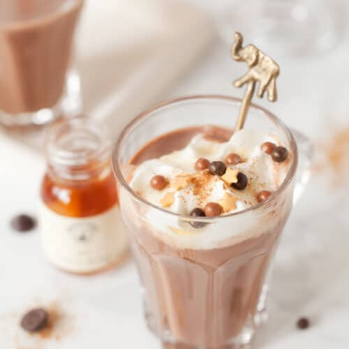 Maple & Bourbon Hot Chocolate in a glass with whipped cream, maple syrup, ground cinnamon and chocolate sprinkles