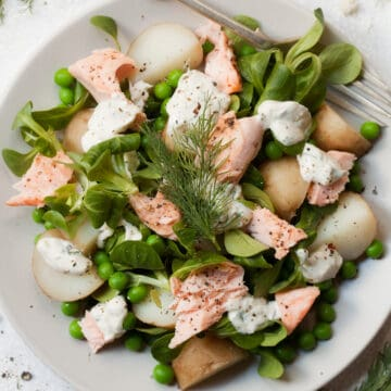 Salmon and Potato Salad with Horseradish Dressing with peas, lambs lettuce and dill served on a white place setting